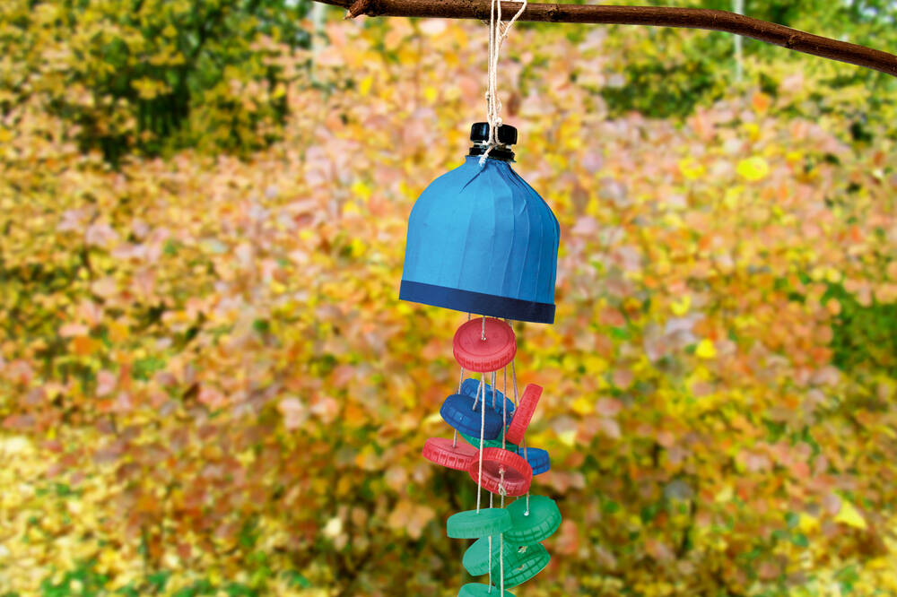 A recycled wind chime hangs on a tree branch in front of an autumn coloured background