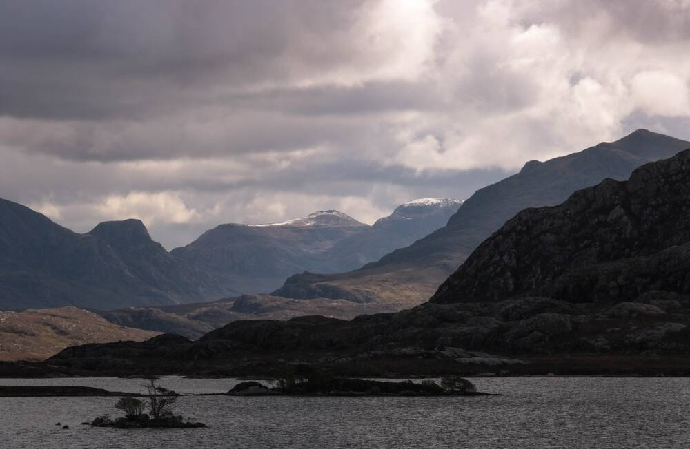 A view of a loch with islands scattered throughout it and mountains in the background. The skies are heavy with clouds.