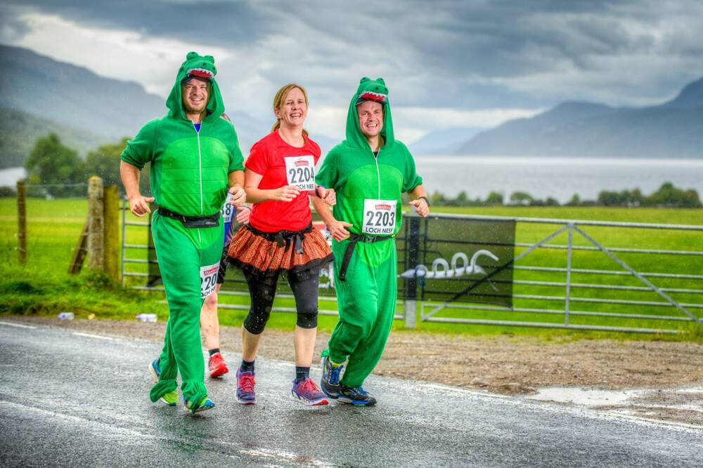 Three marathon runners, two dressed as Nessie and one in a kilt, smile as they run past the photographer.