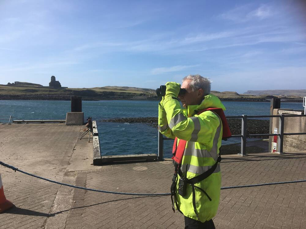 A man dressed in a high-vis coat looks through binoculars out to sea. He stands on a concrete pier. A chapel can be seen on the headland on the opposite side of the bay.