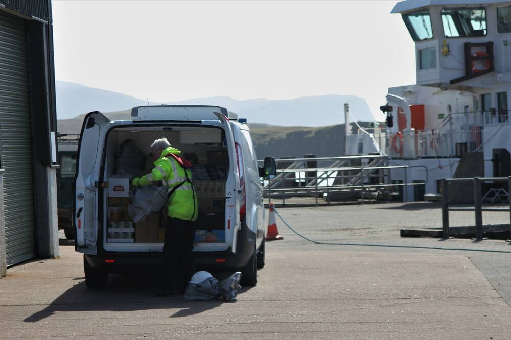 A man unloads supplies from the back of a small white van. It is parked on the tarmac area of a port, with a boat docked in the background.