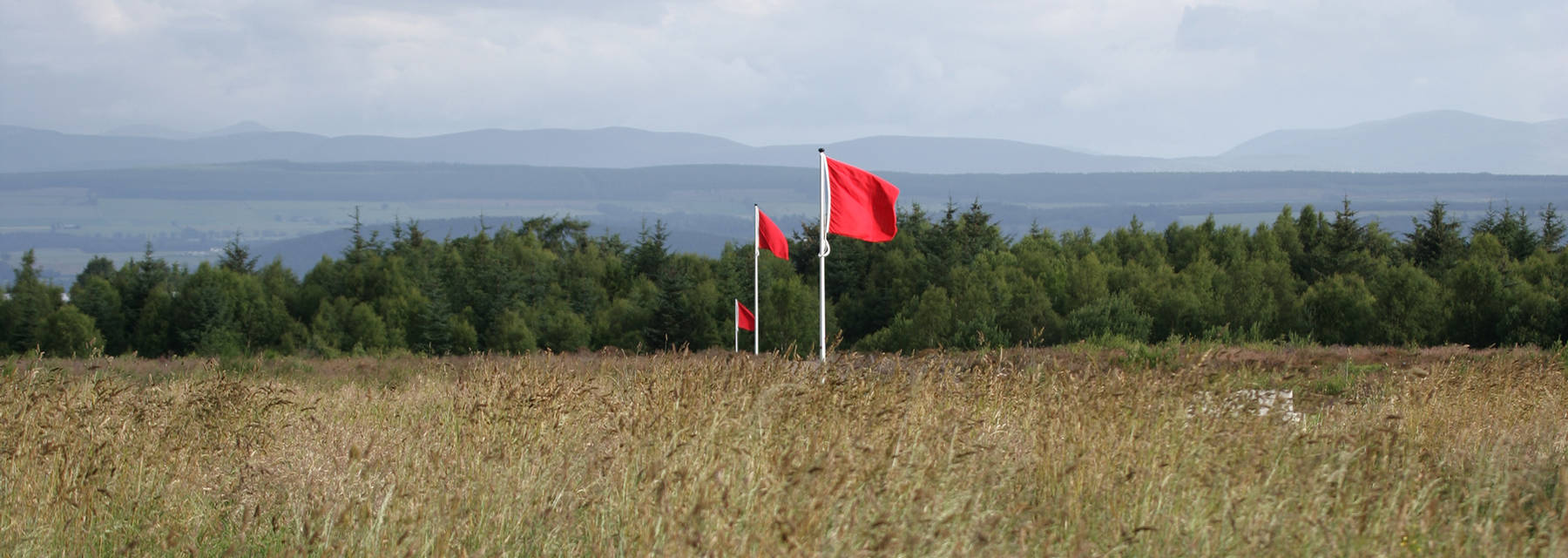 Culloden Battlefield with red flags blowing in the wind