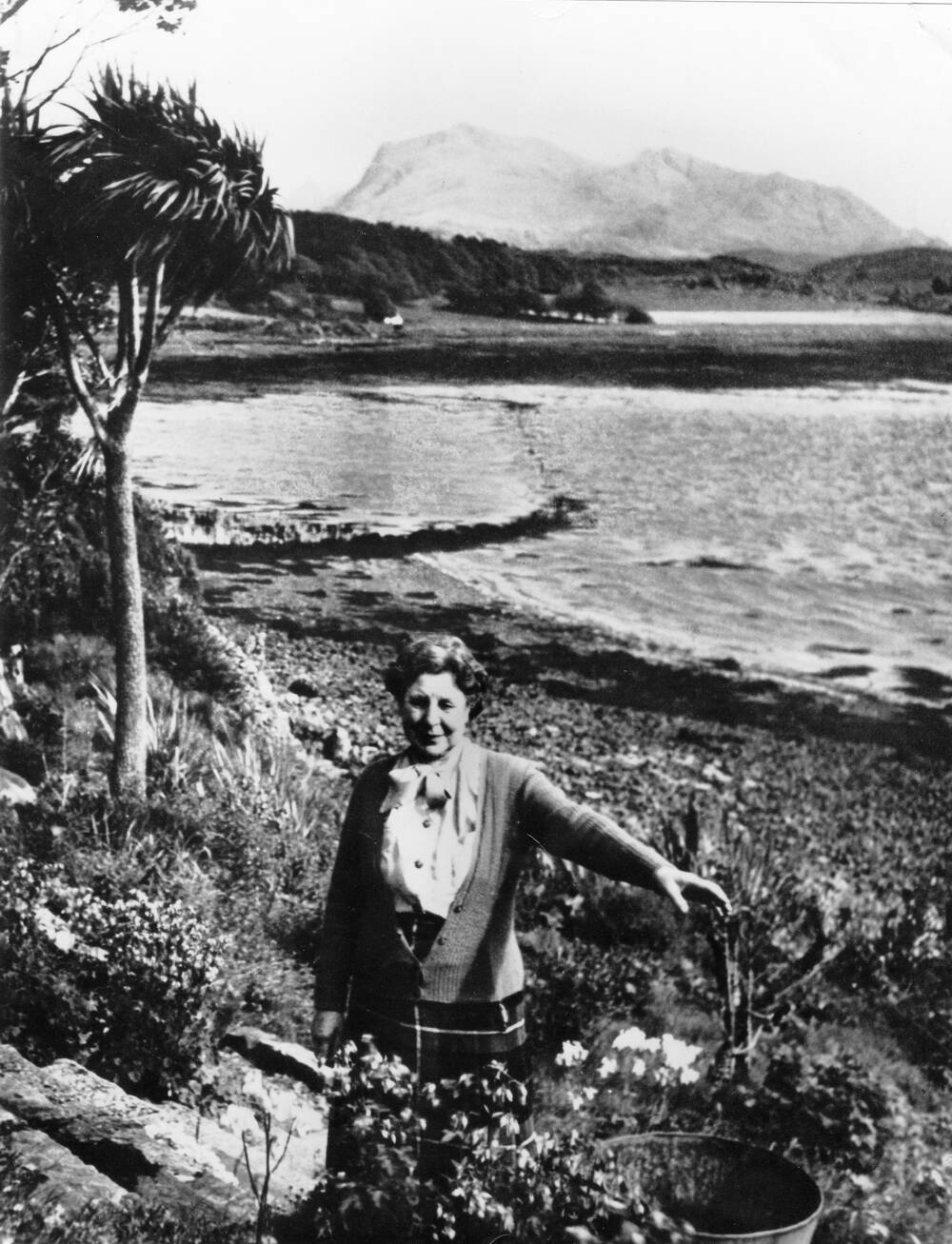 A black and white photograph of Mairi Sawyer pictured in the rock garden she created. The loch and mountains can be seen in the background.