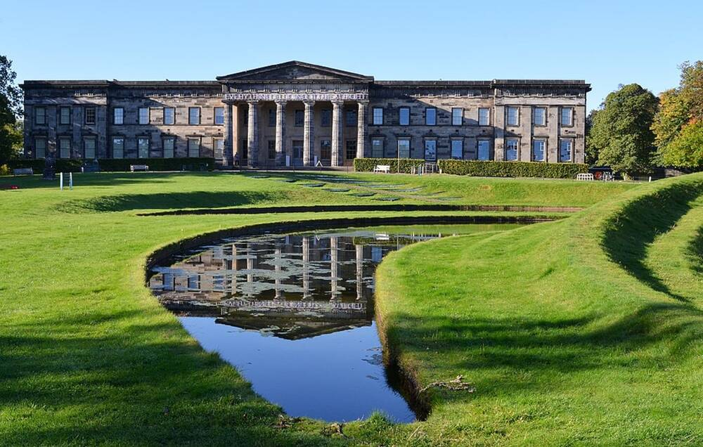 A view of the columned Gallery of Modern Art in Edinburgh. A lawn and curved pond lie in the foreground. The building is long and rectangular, with two storeys of windows visible.