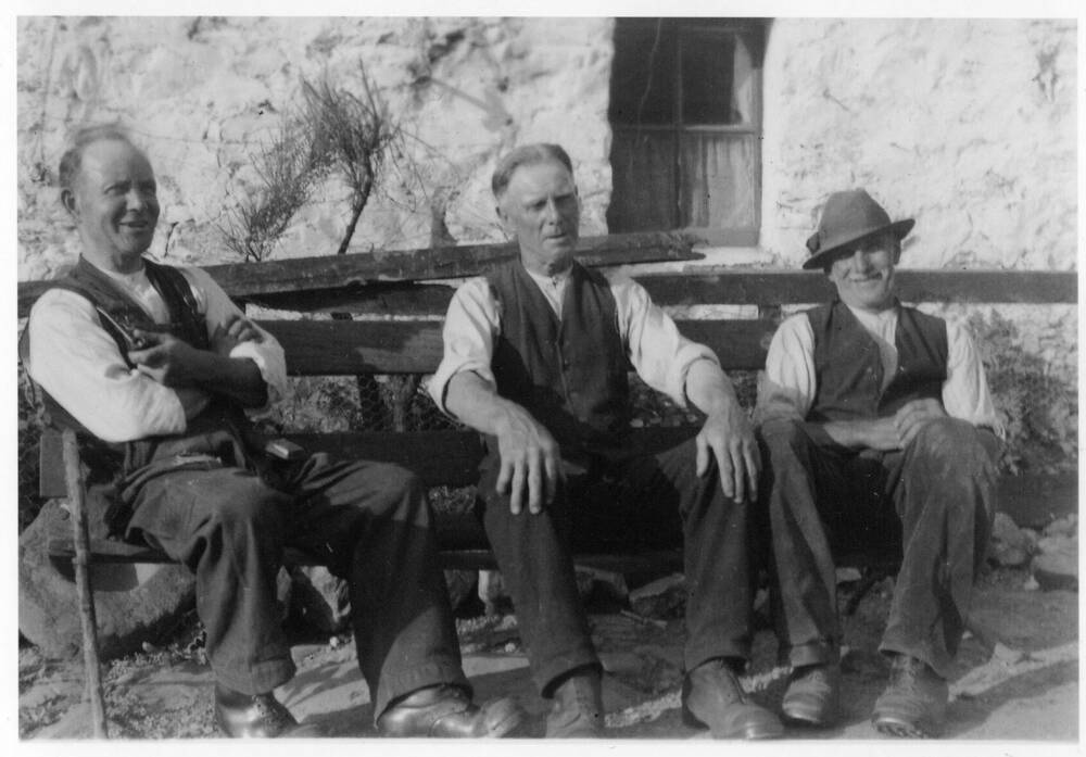A black and white photograph of three men resting on a rather ramshackle bench outside Moirlanich Longhouse. The left end of the bench is higher than the right. The man on the left leans against a stick. The man in the middle rests his hands on his knees. The man on the right wears a hat and smiles directly at the camera.