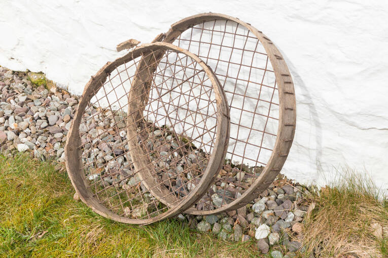 A stone riddle found at Moirlanich Longhouse. It is made up of what looks like two circular tennis rackets (with no handles!) - the smaller sits inside the larger and can be twisted to adjust the size of stones that fall through.
