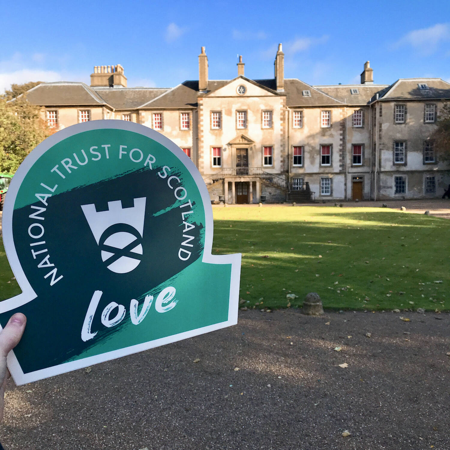 A hand holds a Trust omega-shaped sign (stating LOVE) in front of Newhailes House
