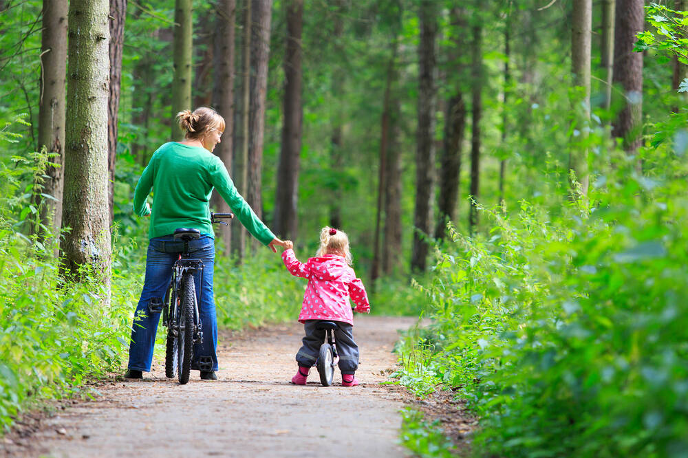 Mother and daughter cycling through Newhailes woodland trail