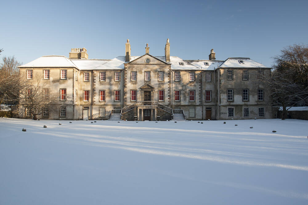 Newhailes House & Gardens on a sunny winter's day. The house stands in the centre of the image with snow covering the roof. In the foreground are the smooth, snow-covered lawns. Large stones marking the edge of the driveway are just visible.