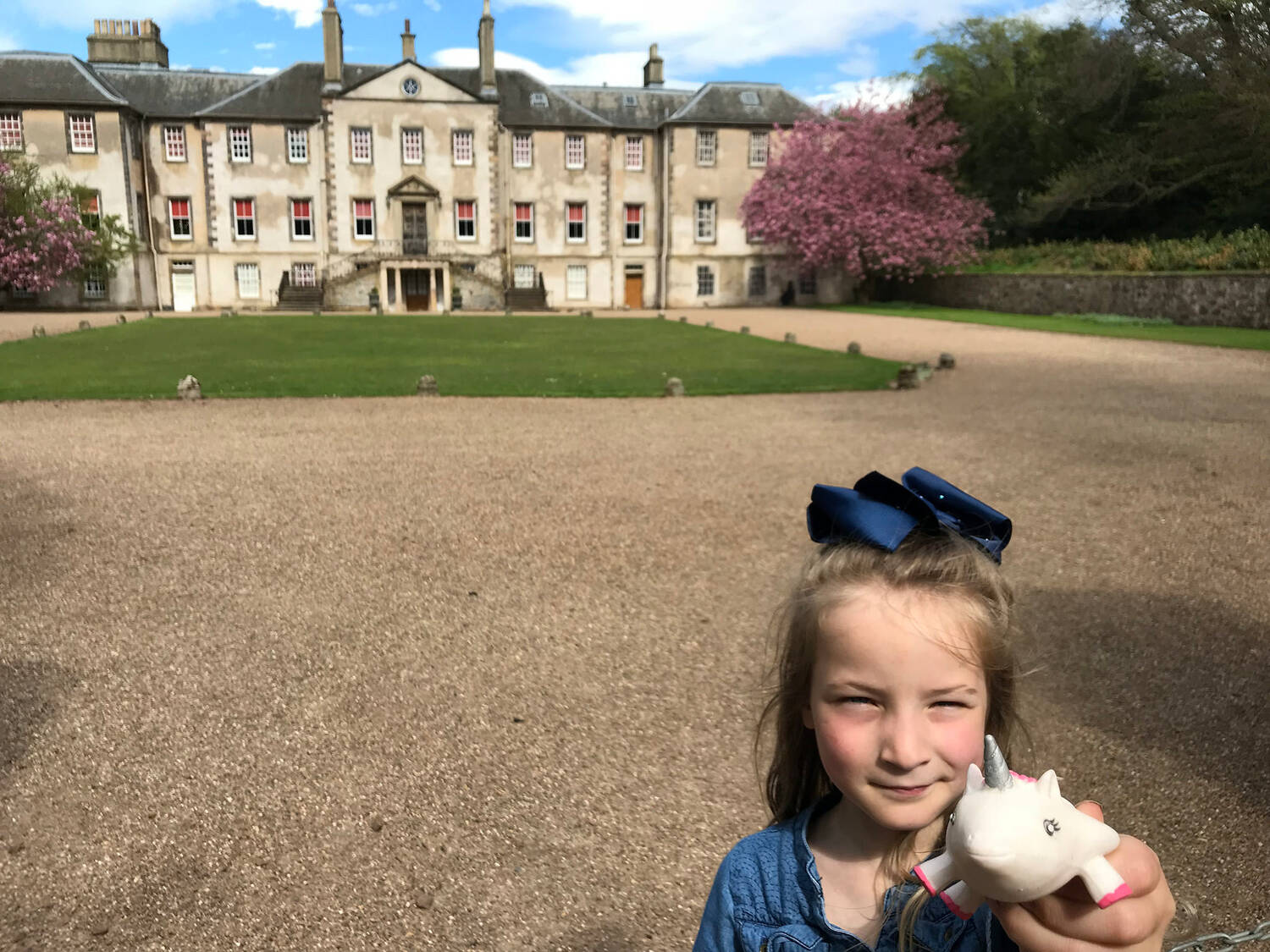Emma and Ursula the Unicorn stand in front of Newhailes House on a sunny spring day.