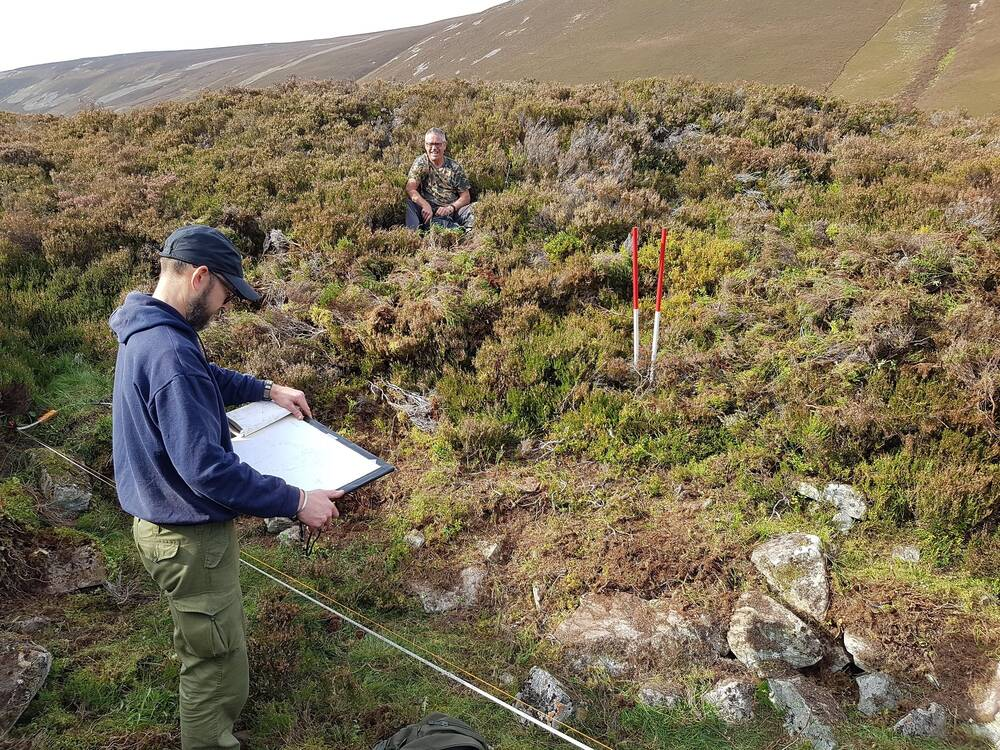 Two men work on a heather-covered landscape. One man sits in the heather, smiling. The other man, closer to the camera, holds a sketch pad. In front of him is a taped area with two red marker depth poles.