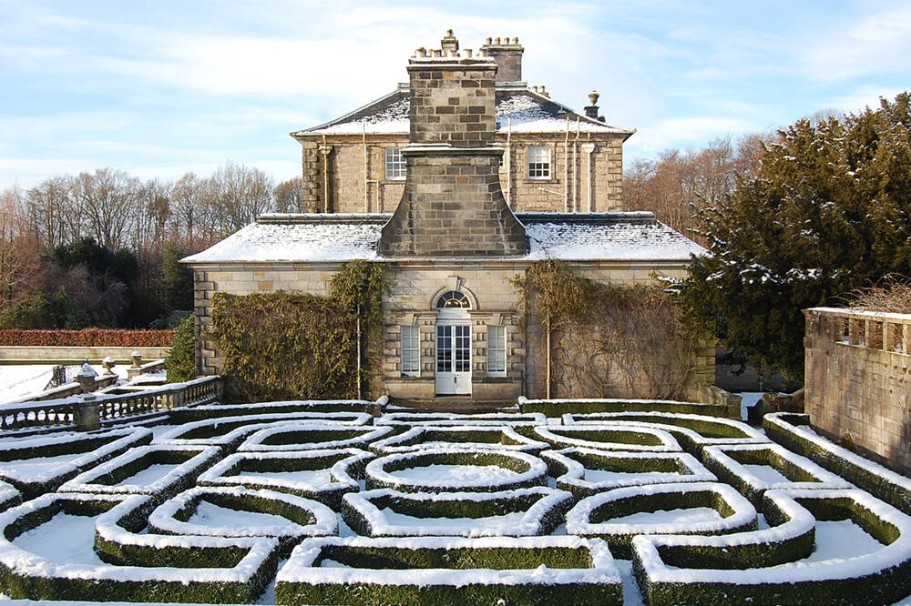 Pollok House from the east. The hedges of the parterre garden are covered with snow.