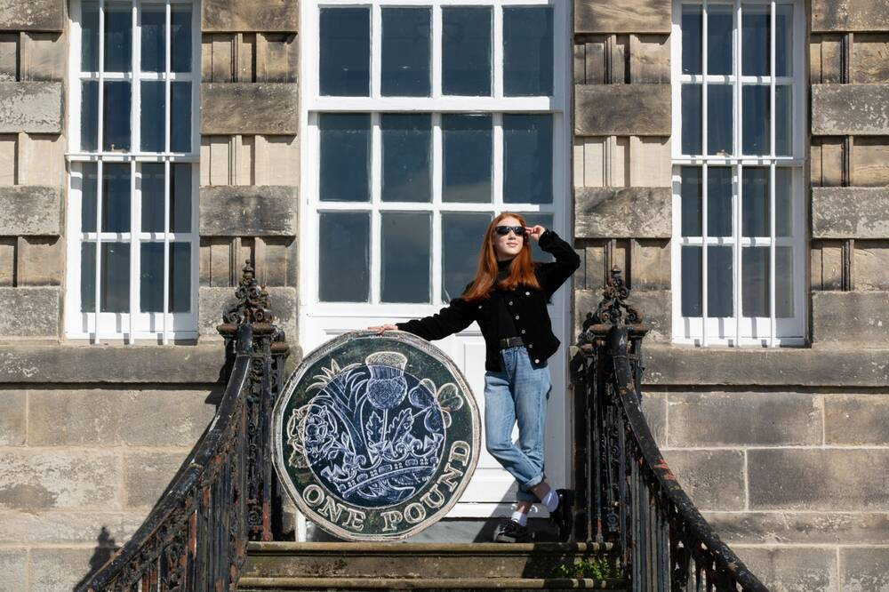 Cherry stands on the steps of Pollok House, looking to her left and shielding her eyes from the sun. With the other hand, she supports a giant pound coin on the top step.