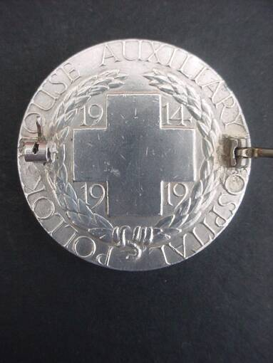 The reverse of the silver medal, with a large cross at the centre and the dates 1914 and 1919 embossed. Around the rim it reads: Pollok House Auxiliary Hospital. The badge fixings can also be seen.