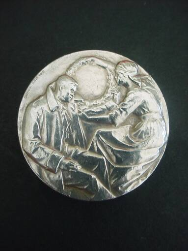 A silver medal, with an embossed decoration of a lady holding a large laurel wreath over a seated soldier. The soldier is holding his arm out towards the nurse.