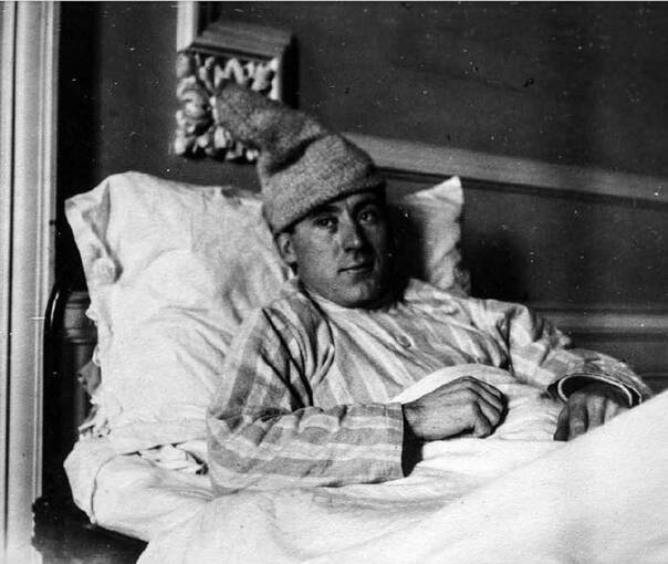 A man lies propped up in bed, wearing striped pyjamas. He also has a large woolly hat on his head.