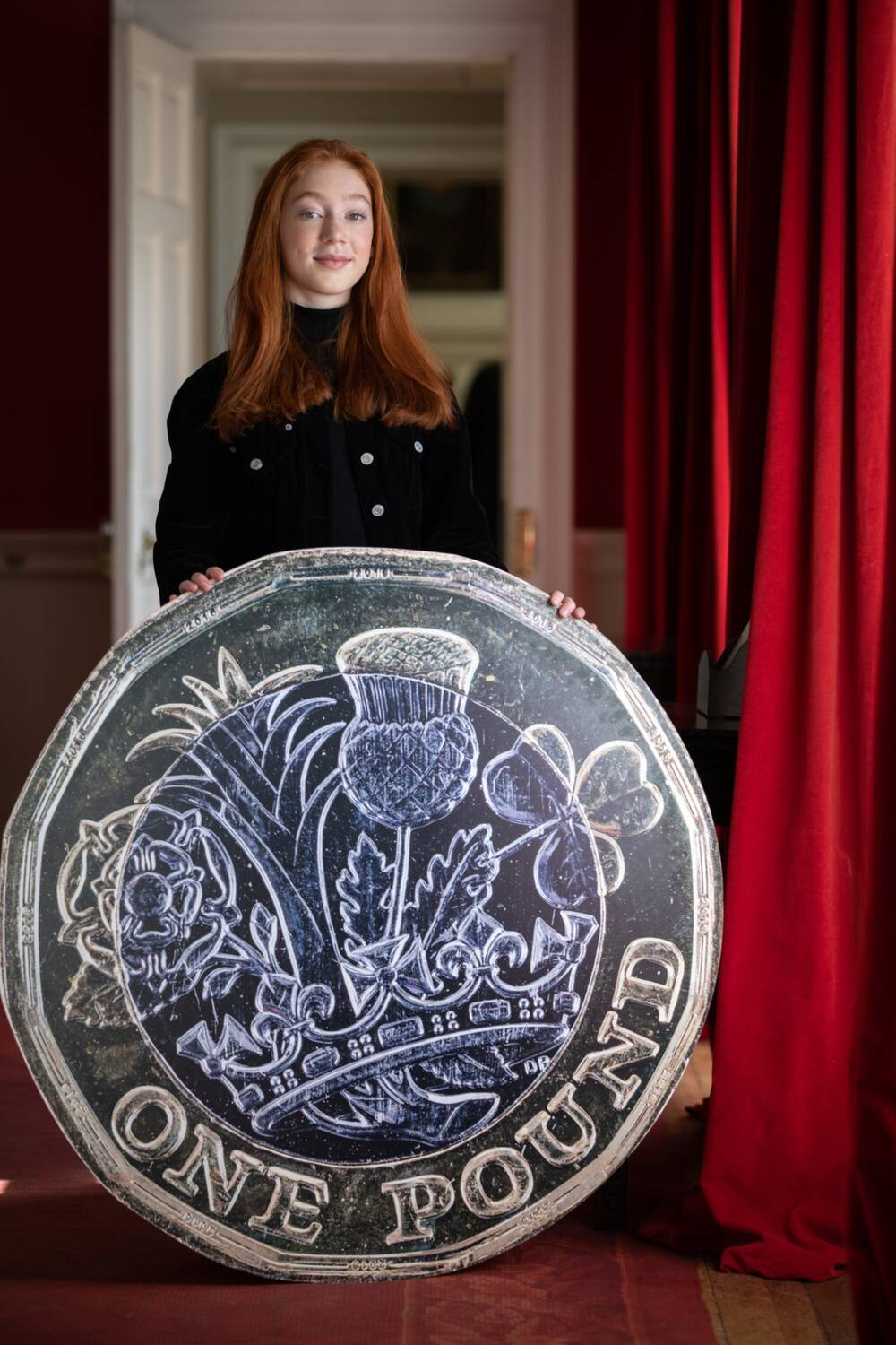 Cherry stands inside Pollok House, beside a floor-length red curtain, holding a giant pound coin.