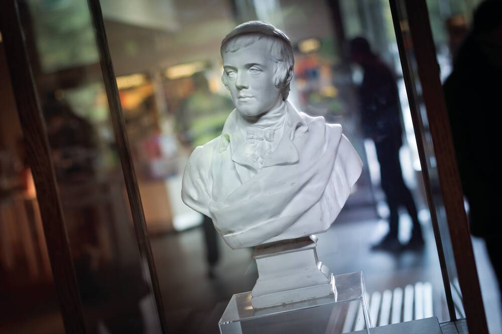 A white-coloured bust of Robert Burns in a display case in a museum.