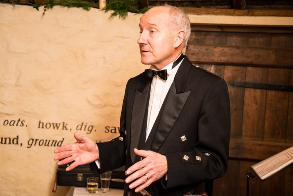 A formally dressed man gives a speech at a Burns Supper.