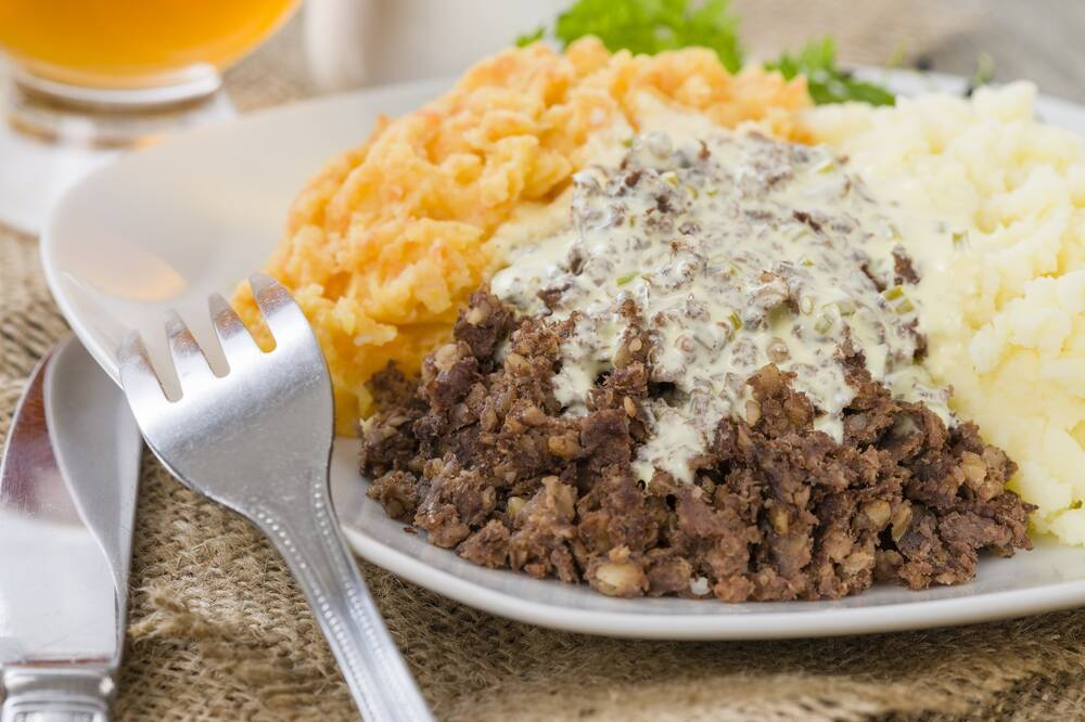 A plate of haggis, neeps and tatties, with whisky sauce poured over the top.