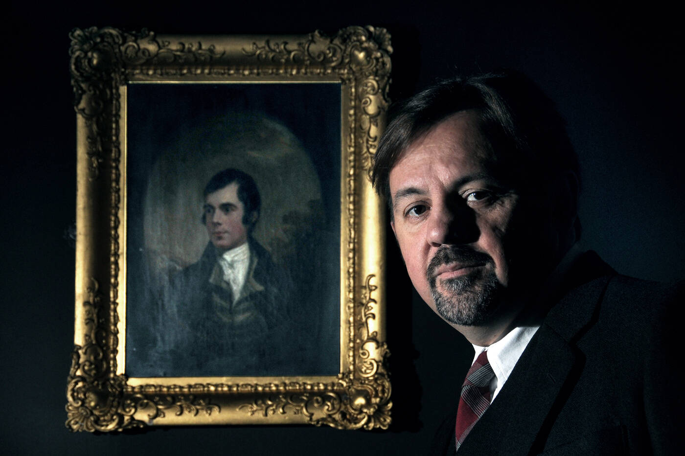 Rab Wilson standing next to a portrait of Robert Burns