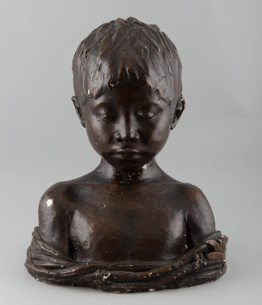 A brown bust of a young boy. The boy has his eyes cast down, and has a piece of fabric wrapped across his arms and chest.