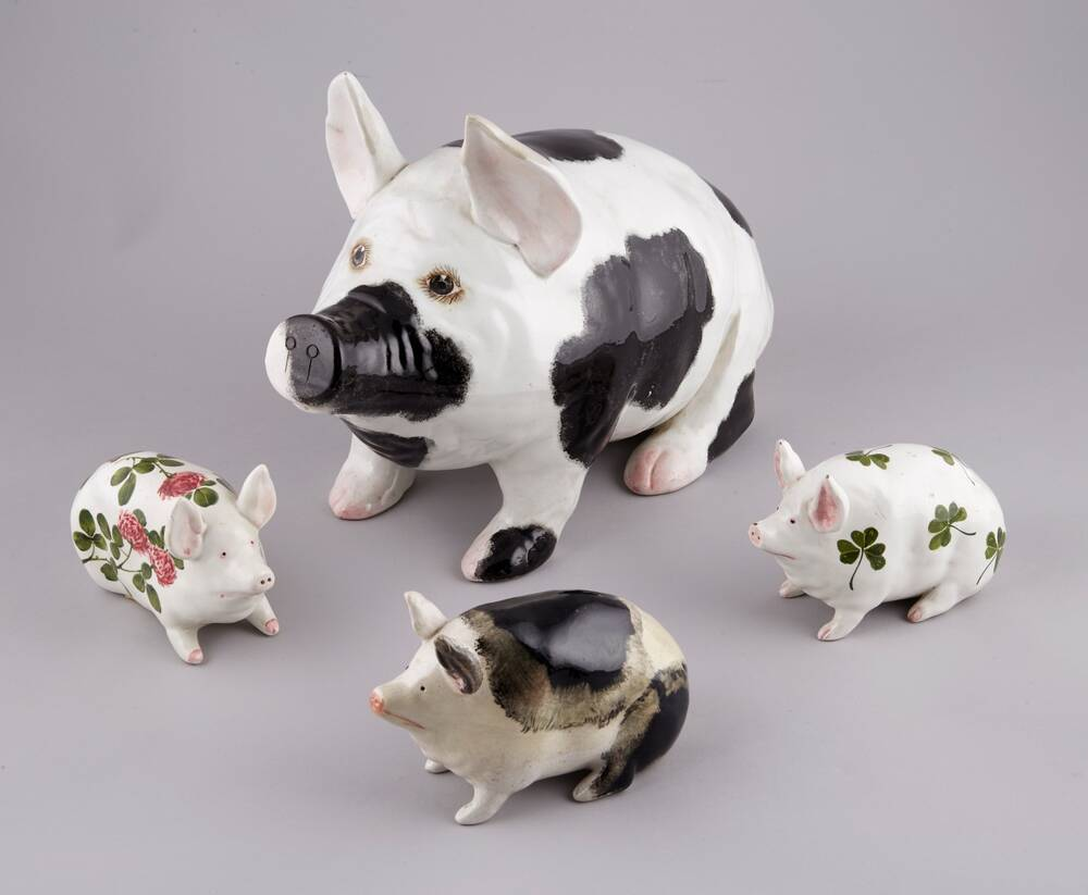 Four Wemyss Ware pigs, one large one and three small ones.