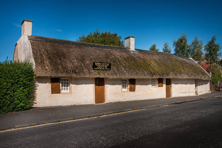 Burns Cottage on a sunny day. The thatched cottage with white stone walls is seen from the road.