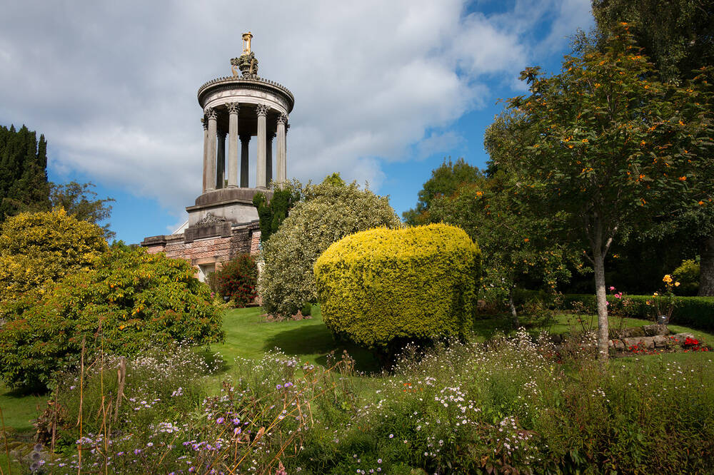 Looking up at Burns Monument from the gardens against a blue sky with clouds