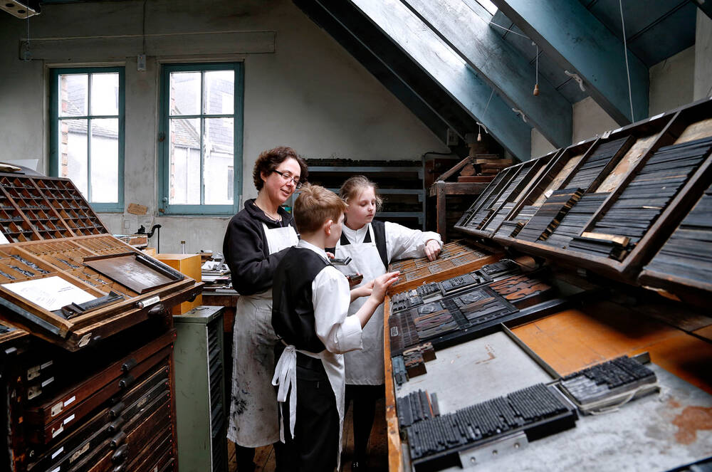 Two children and a woman stand around a large case in a printing workshop. All wear long white aprons.