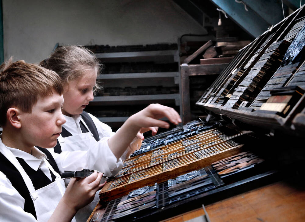 Children in the case room at Robert Smail's Printing Works