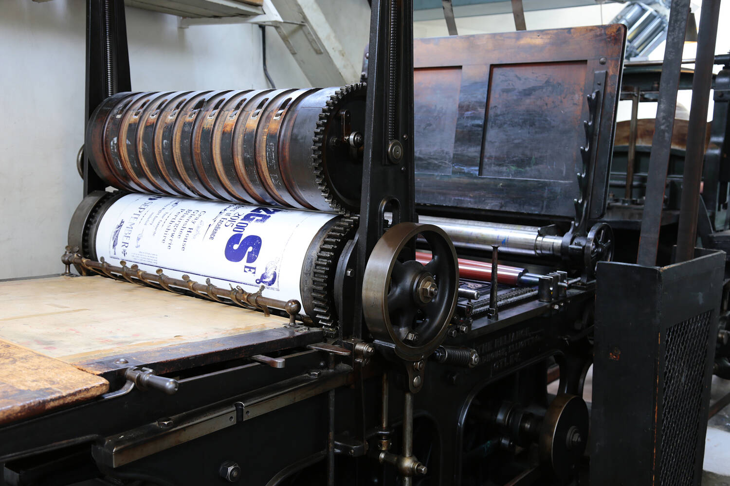 A close-up view of the Wharfedale reliance printing press, showing a large poster rolled around a wheel.