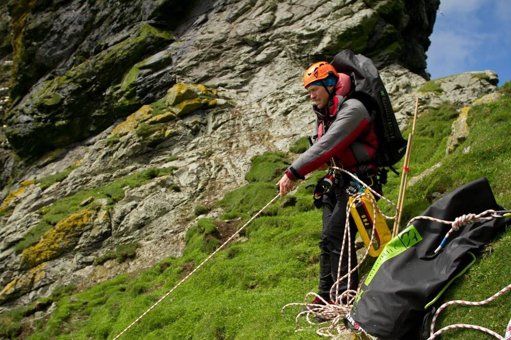 A man holds a rope taut on the side of a cliff. He wears a helmet, and climbing equipment lies on the ground beside him.