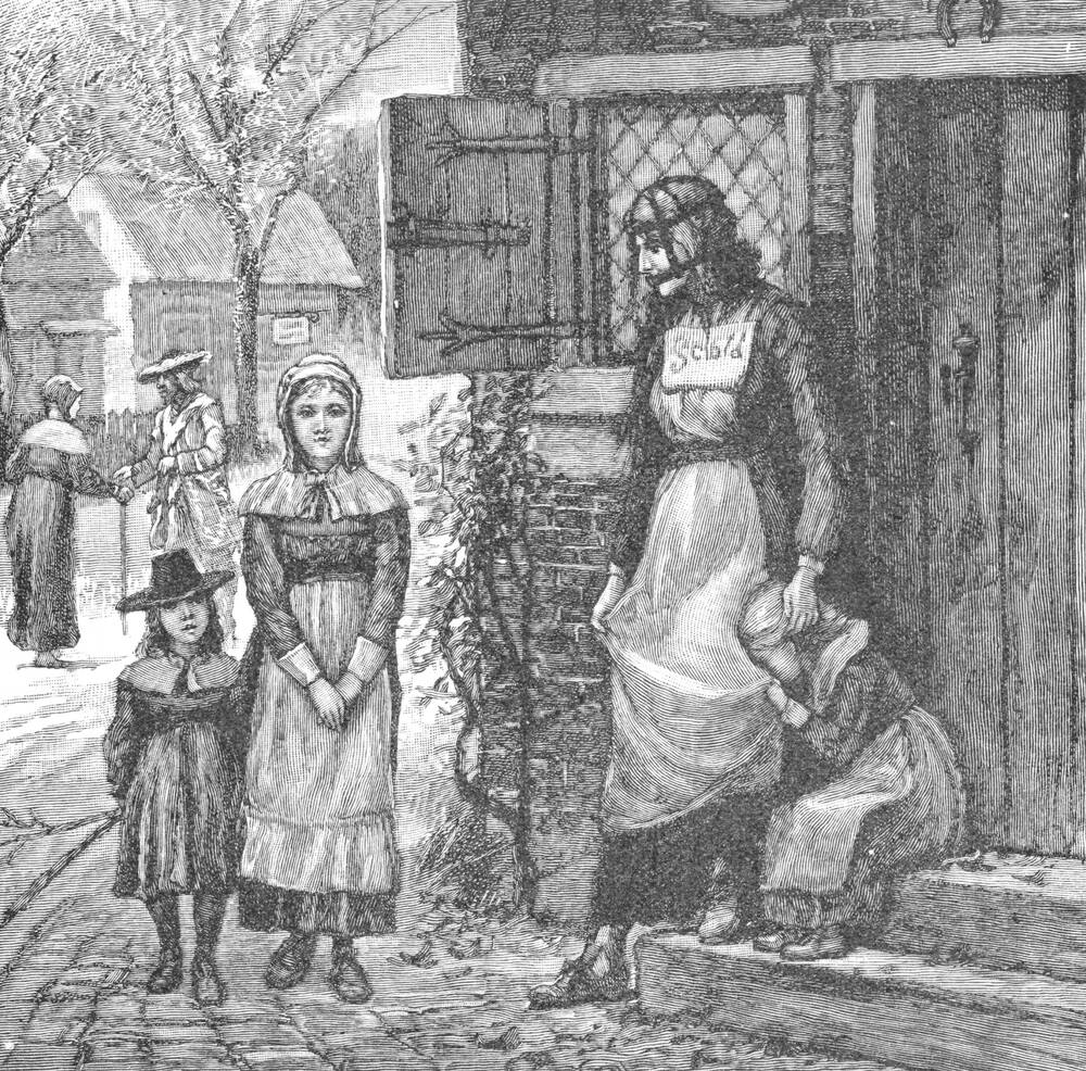 A black and white line engraving featuring a woman and her three children, all standing outside a house on a street. The woman wears a scold's bridle over her head, and has a white sign stitched to the front of her dress that says: Scold. Two of the children stand in the street with an impassive expression. The third, younger, child sits on the house steps and buries her face in her mother's apron. She appears very upset.