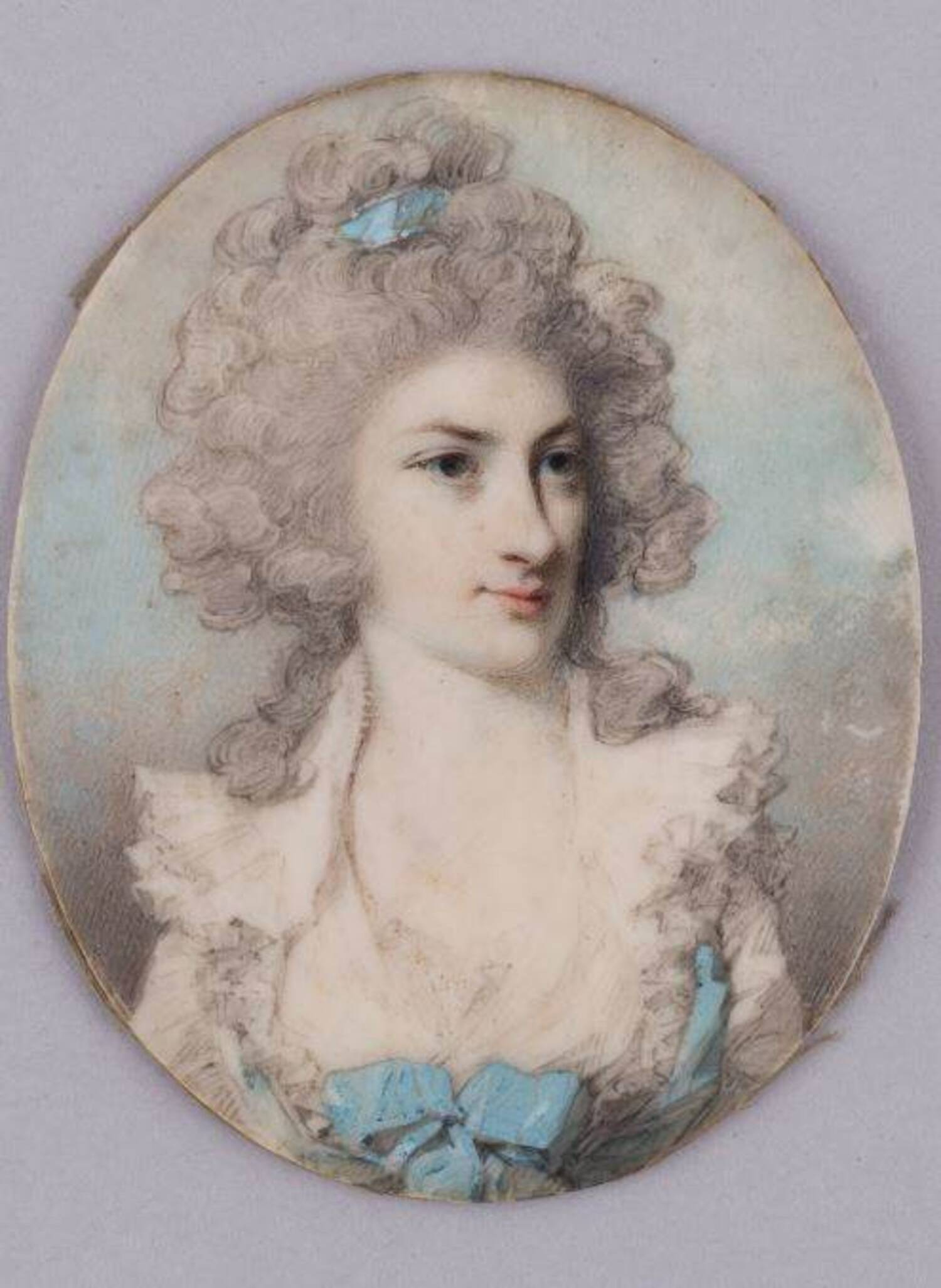 An oval-shaped portrait miniature of a young woman. She has powdered white hair, which is piled on top of her head and fastened with a blue ribbon.