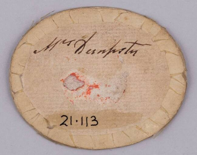 The reverse of an oval-shaped portrait miniature. The miniature is backed in brown paper and 'Mrs Dempster' is written near the centre in black ink.