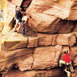 Three men climbing a rockface
