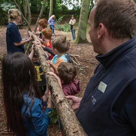Trust ranger with group of children moving a large timber