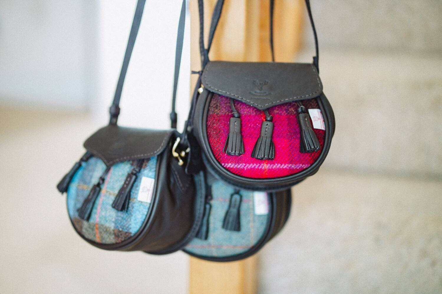 Three sporran-shaped handbags hang from a banister post by some carpeted stairs. The bags have a tartan body with leather tassels and strap.