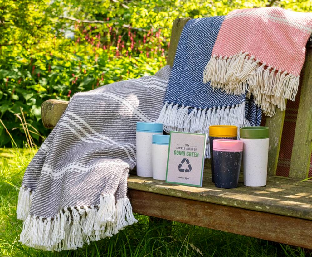 Woollen rugs and blankets are displayed draped over a wooden bench in a sunny garden. On the seat of the bench is also a range of recycled and reusable coffee cups and a book with green tips.