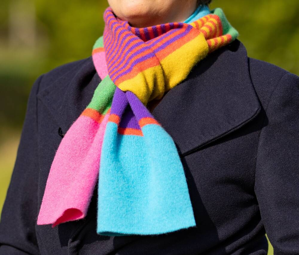 A close-up of a colourful wool scarf, worn around the neck of a model in a navy jacket.