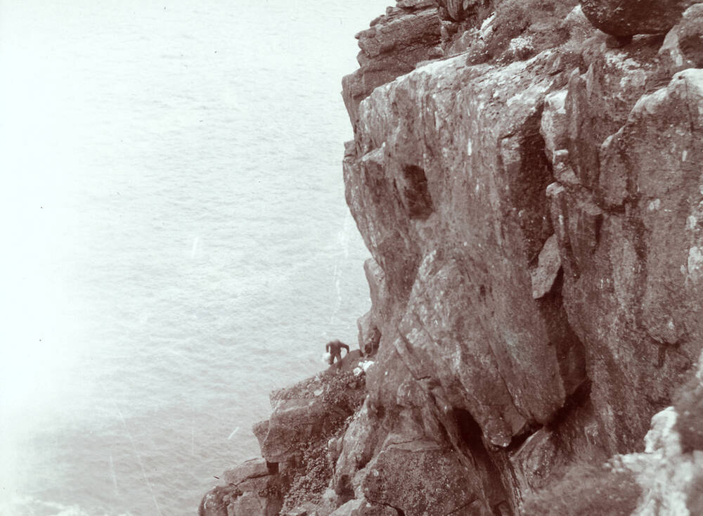 A man climbing over rocks at St Kilda; photographed by R Milne in 1907