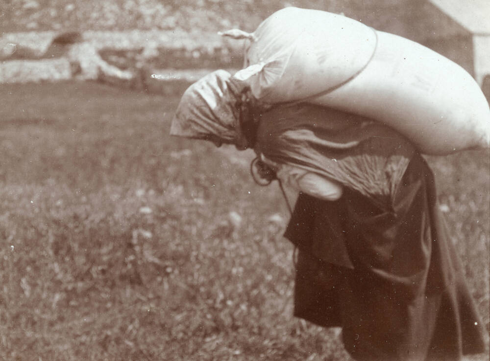 A St Kilda woman carrying a sack over her shoulder; photographed by R Milne in 1907