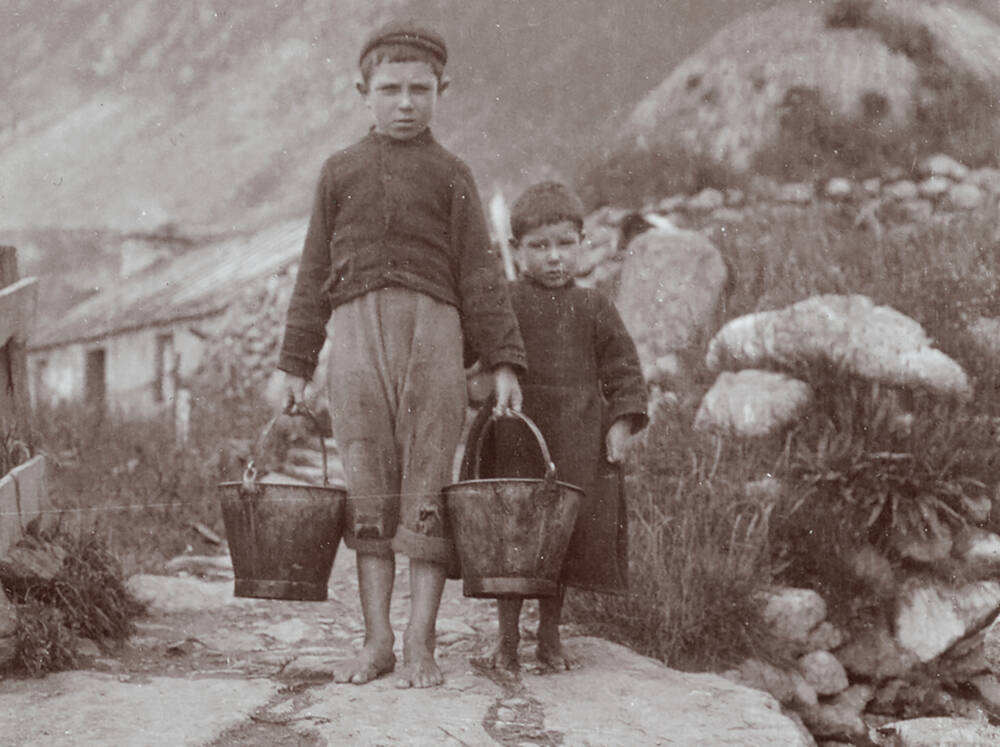 Two St Kilda children carrying buckets; photographed by R Milne in 1907