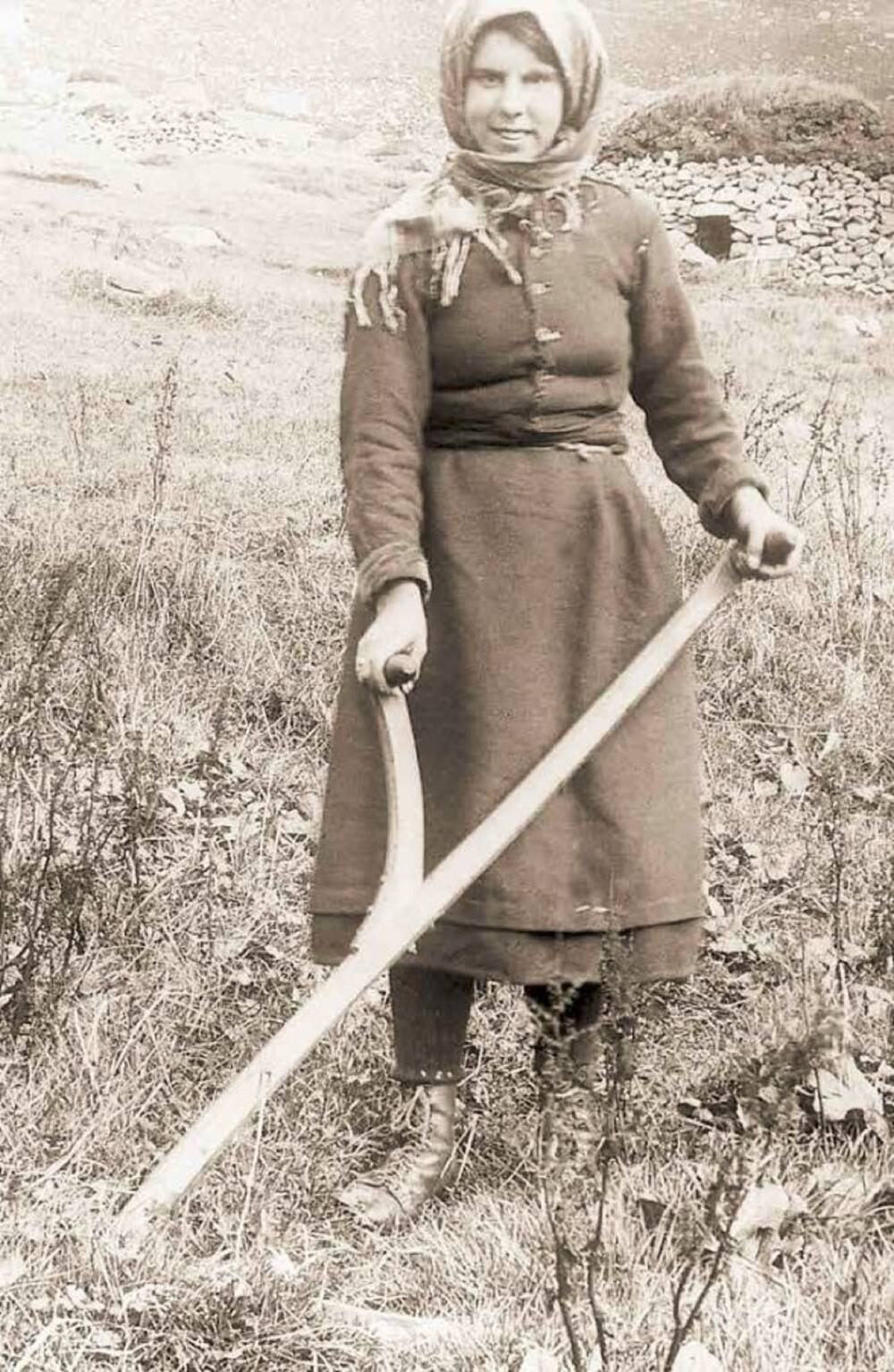 A sepia photograph of a young woman standing in a field and holding a scythe. She wears a jacket and long woollen skirt, with boots. She also wears a scarf wrapped around her head.