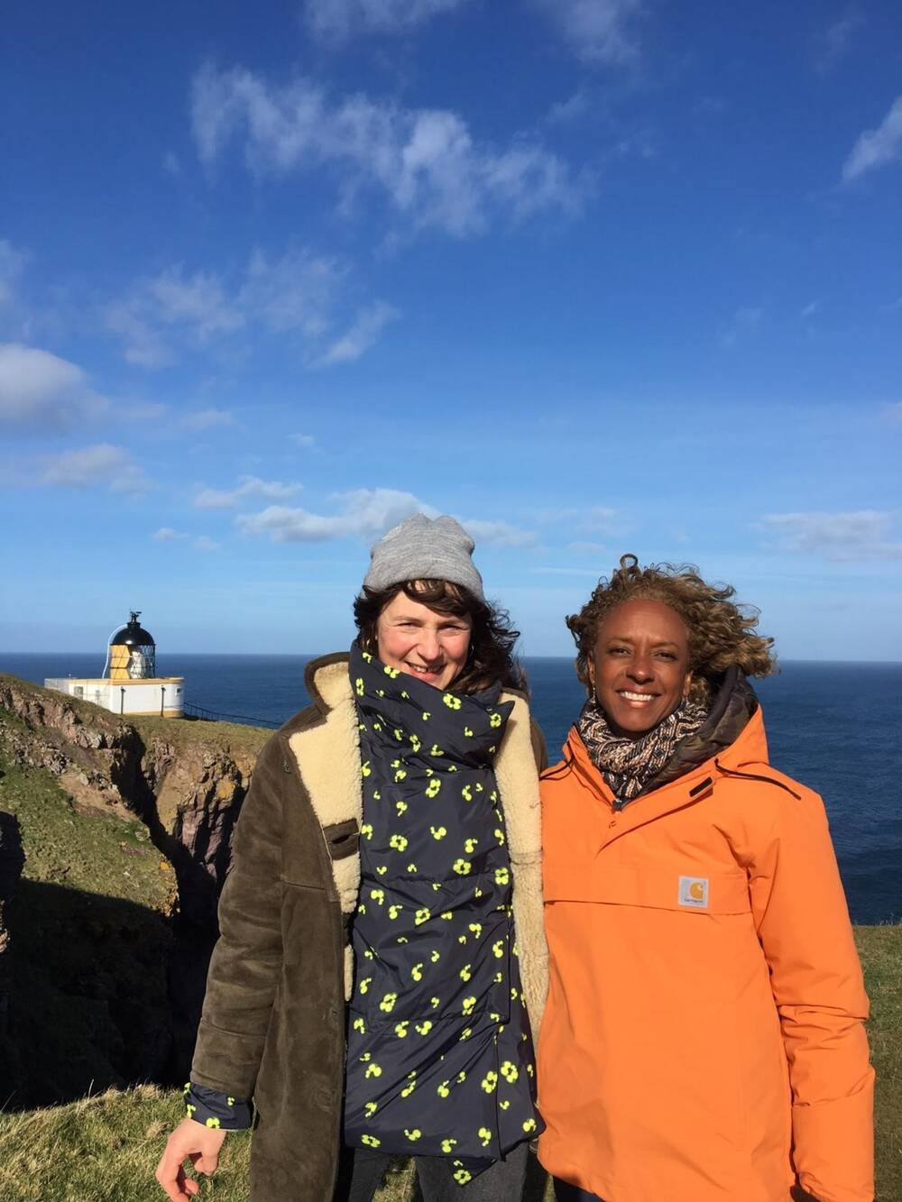Sarah and Gillian stand on the cliffs at St Abb's Head with the lighthouse in the background.