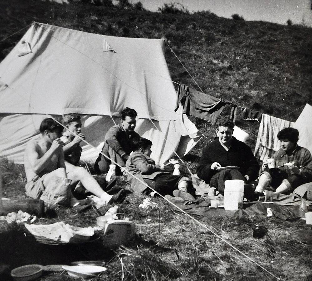 A black and white photo of a group of people sitting in front of a tent, eating and drinking. Clothes are stretched over the guy ropes to dry.