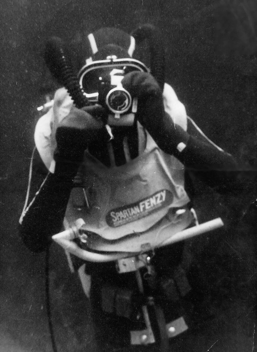 A black and white photo of a diver underwater, holding up a camera to his mask.