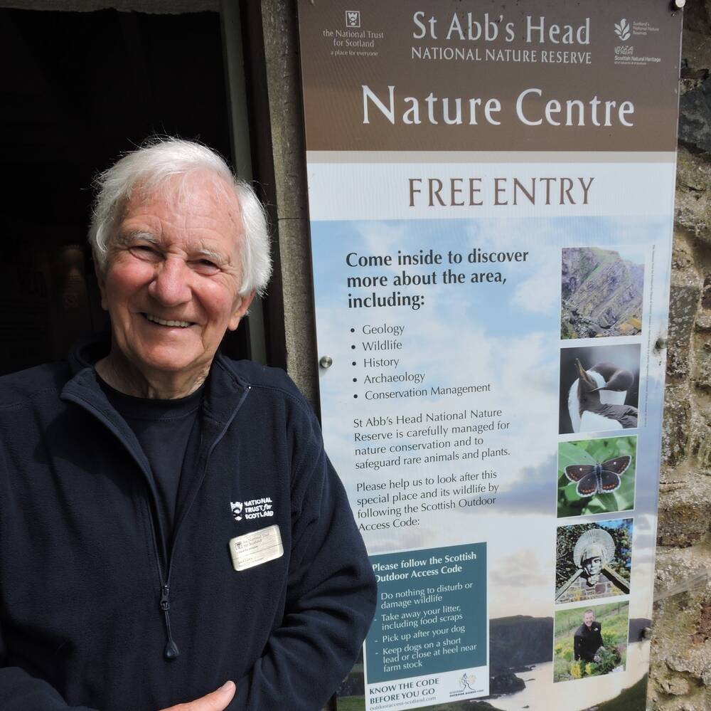 A man stands in a doorway next to an information board about St Abb's Head NNR Nature Centre. He is smiling.