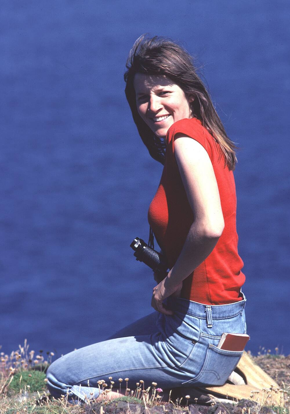 A lady kneels on a cliff top and smiles towards the camera. She wears a pair of binoculars around her neck.